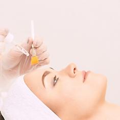 Une patiente reçoit un traitement de peeling chimique sur le visage par une esthéticienne
