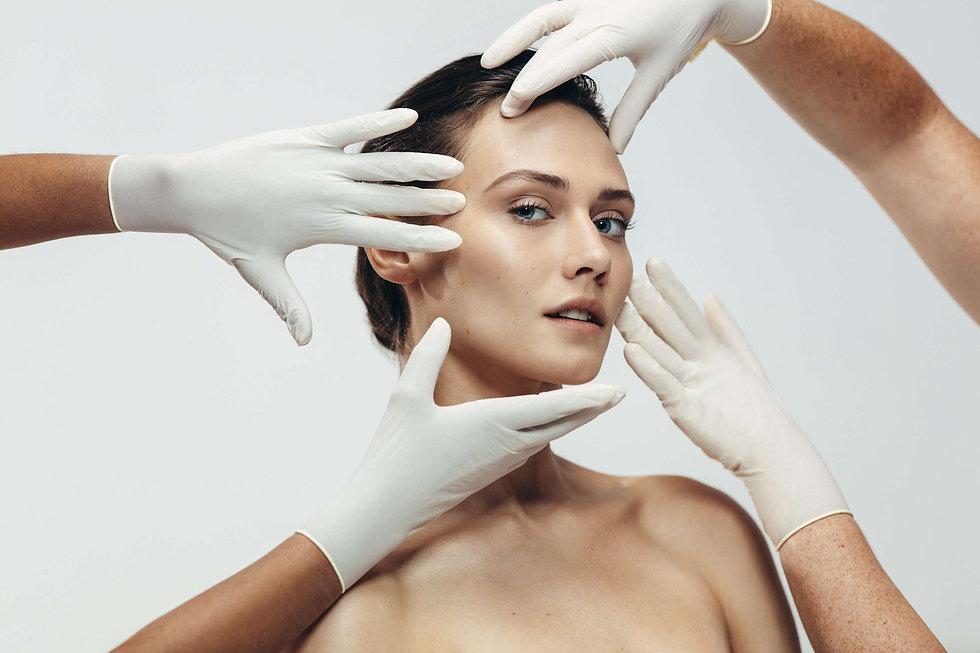 Visage avec des mains en gants chirugicaux
