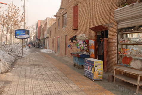 """In January 2008, when back in Kashgar for the first time in nearly 6 years, I suddenly recognised that I was in the same spot. The facades had changed, but the basic spatial arrangements were still the same.   The man sweeping the pavement outside his shop confirmed that he owned the house above, as he had done at the time of demolition. Visibly suppressing his bitterness, he said """"the Communist Party gave me 6000 renminbi [in compensation]—it wasn't even enough to rebuild the wall.""""   He corrected my guess that he had three daughters and one son of the ages that I estimated. Now, he said, he had two sons.   """"You want to go inside my house?"""" It was hardly a question. """"Go up and have a look,"""" he said, waving his arm briefly upward before going back to his sweeping."""