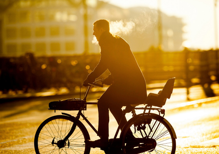 Stylish man caught cycling in the golden sunlight