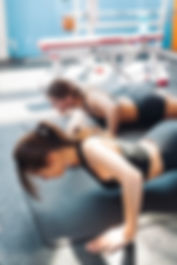 Two woman friends or sportsmen exercising in gym.jpg