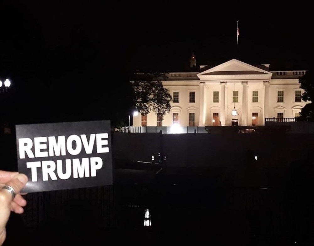 "A hand holds a ""REMOVE TRUMP"" card in front of the White House"