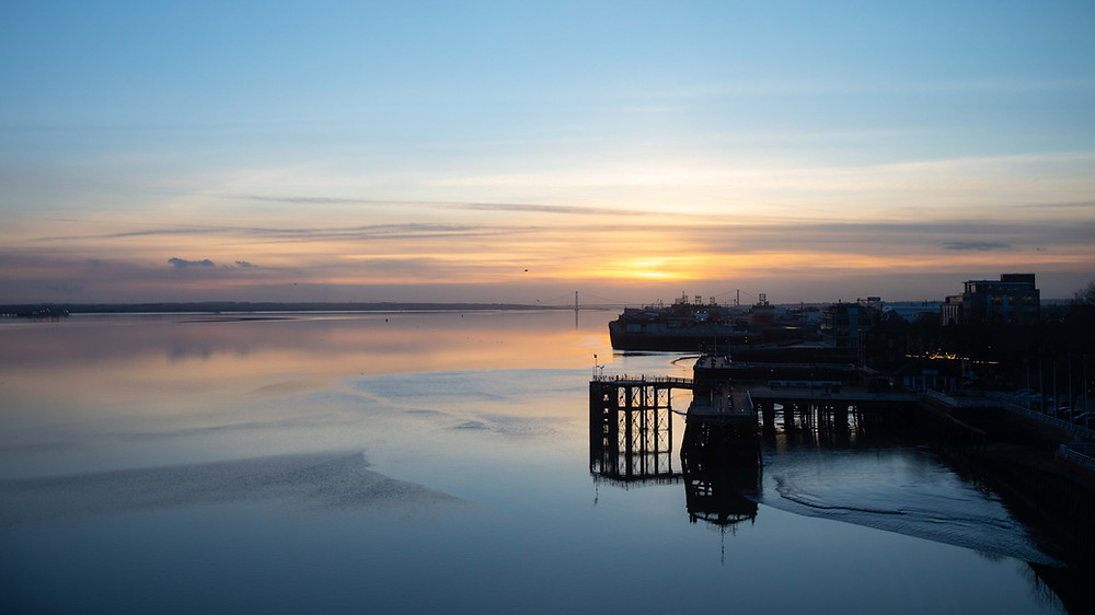 Hull Marina and Victoria Pier in silhouette with calm river Humber reflecting the gentle sunset tones with th Humber Bridge in the background.