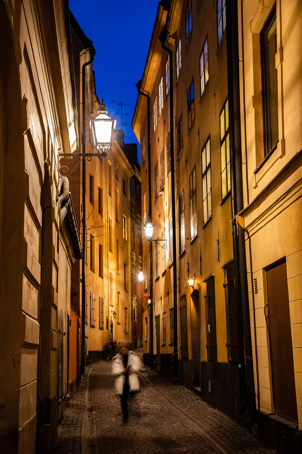 A figure walk along a traditional cobbled street in Gamla Stan, Stockholm.