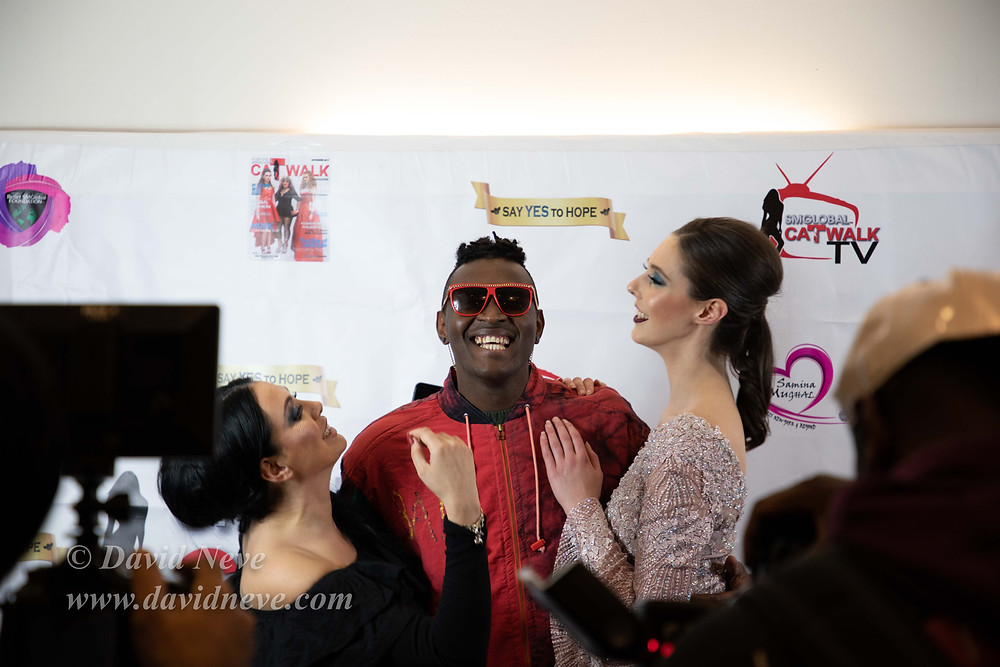 Three models stand in front of SMGlobal's backdrop with the media surrounding them in the foreground whilst the models were smiling and giving positive vibes.