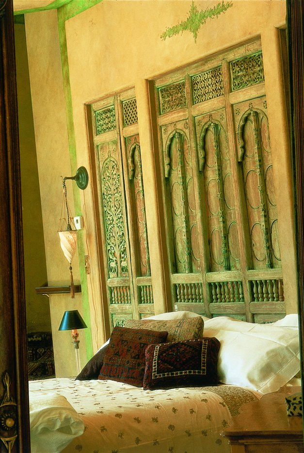 Carved panel serving as dramatic backdrop for the bed