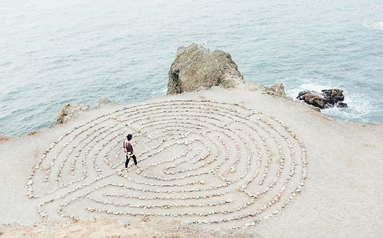 woman walking a labrynth on the beach