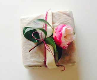 A rose on top of a nicely wrapped gift.
