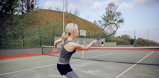 Woman hitting a tennis ball with a tennis racket while on a tennis court