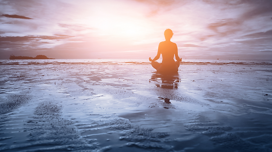 woman sitting on beach meditating in the water