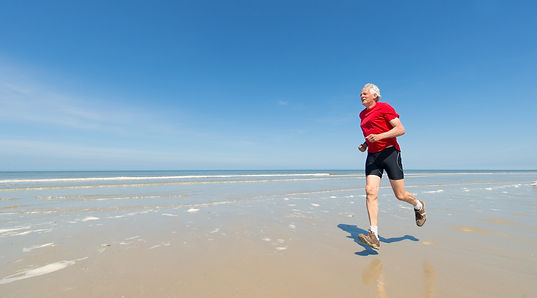 Older man with white hair jogging on the beach