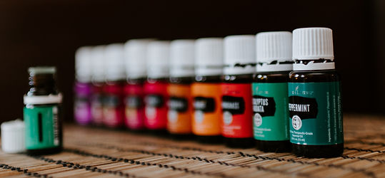 Bottles of essential oils all in a row with different colored labels