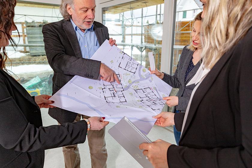 Grundriss einer Siedlung, Nahaufnahme, alle Hände halten den Plan