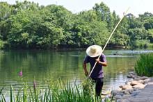 A man cleans a swan pond at the Panda Ba