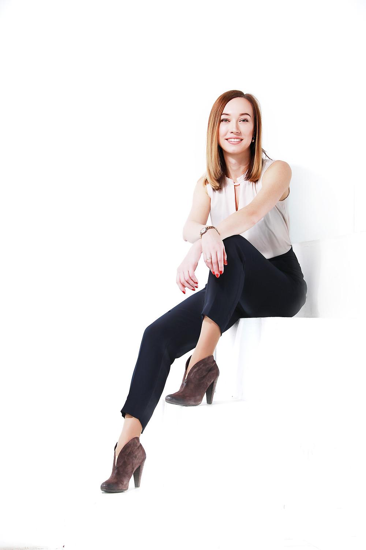 Женский деловой портрет на белом фоне. Эта поза лишь отправная точка для бизнес портрета