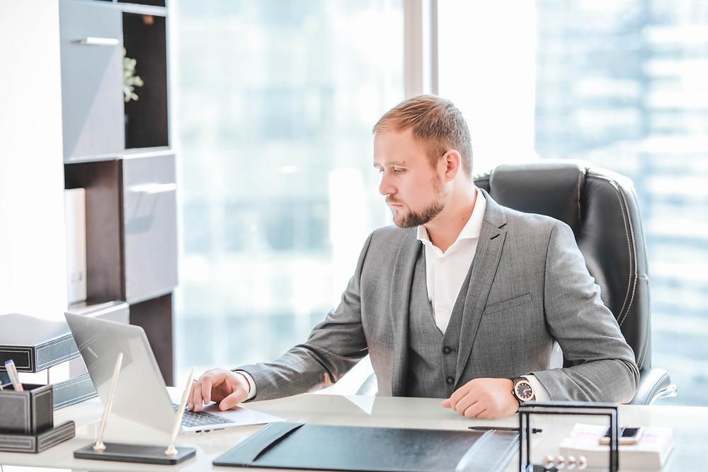 Модный мужской бизнес-портрет делового мужчины в костюме, поясной план. Фото делового мужчины в костюме перед столом в профиль. Бизнес-портреты мужчины из фотосессии в деловом стиле