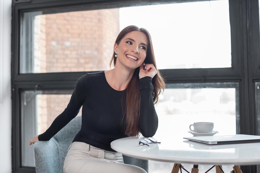 дружественная поза женского бизнес портрета, когда вы сидите на стуле. Деловая женщина на фоне окна