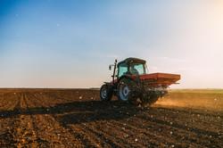 Farmer fertilizing arable land with nitr