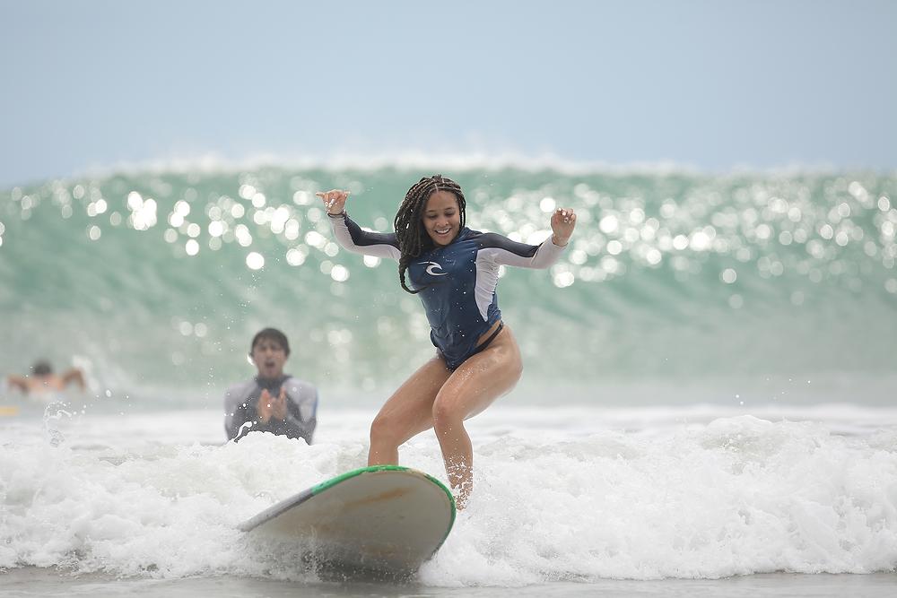 Instructor y alumna en una lección de surf. La alumna ya corrió su solita y está bajando de su tabla de un brinquito en la espuma.