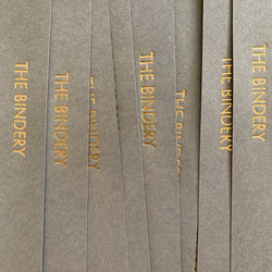 Gold foil stamped gray paper bookmarks that say The Bindery