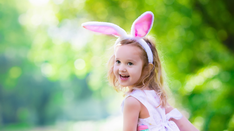 child smiling with bunny ears