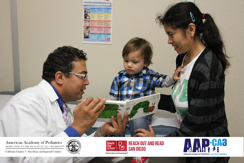 A doctor reads to a young boy sitting with his mother