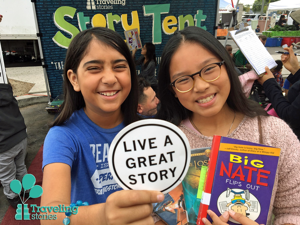 "Two young girls smile with books and a sticker that says ""Live A Great Story"""