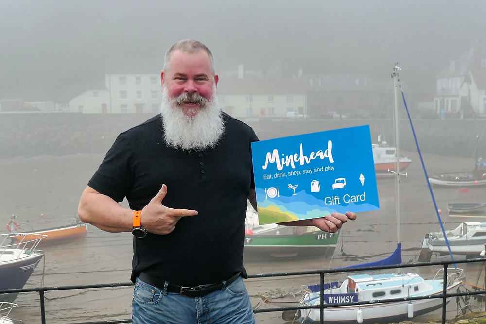 Picture of Julian holding a mock-up of the Minehead Gift Card
