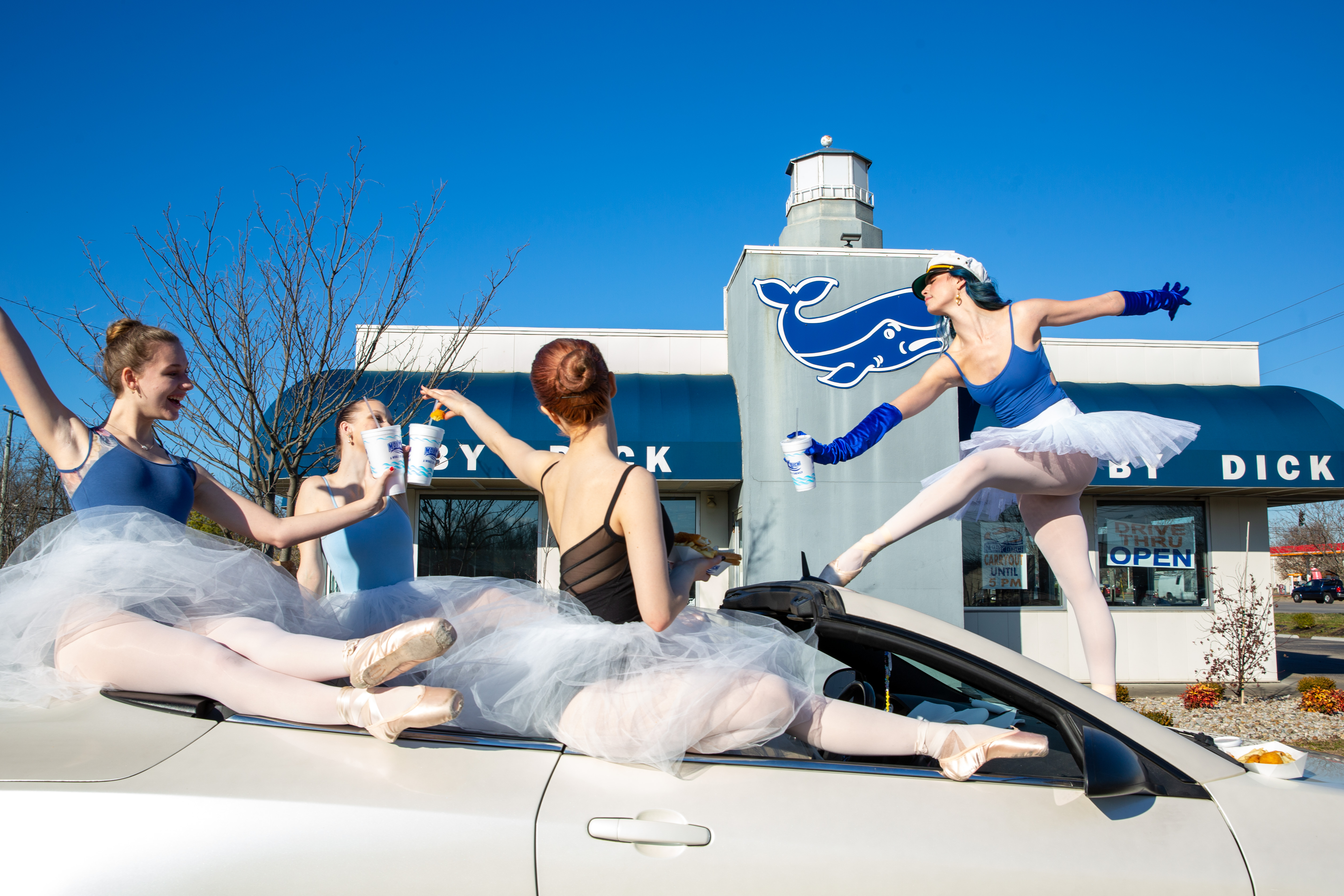 Ballerinas posing outside in front of a restaurant