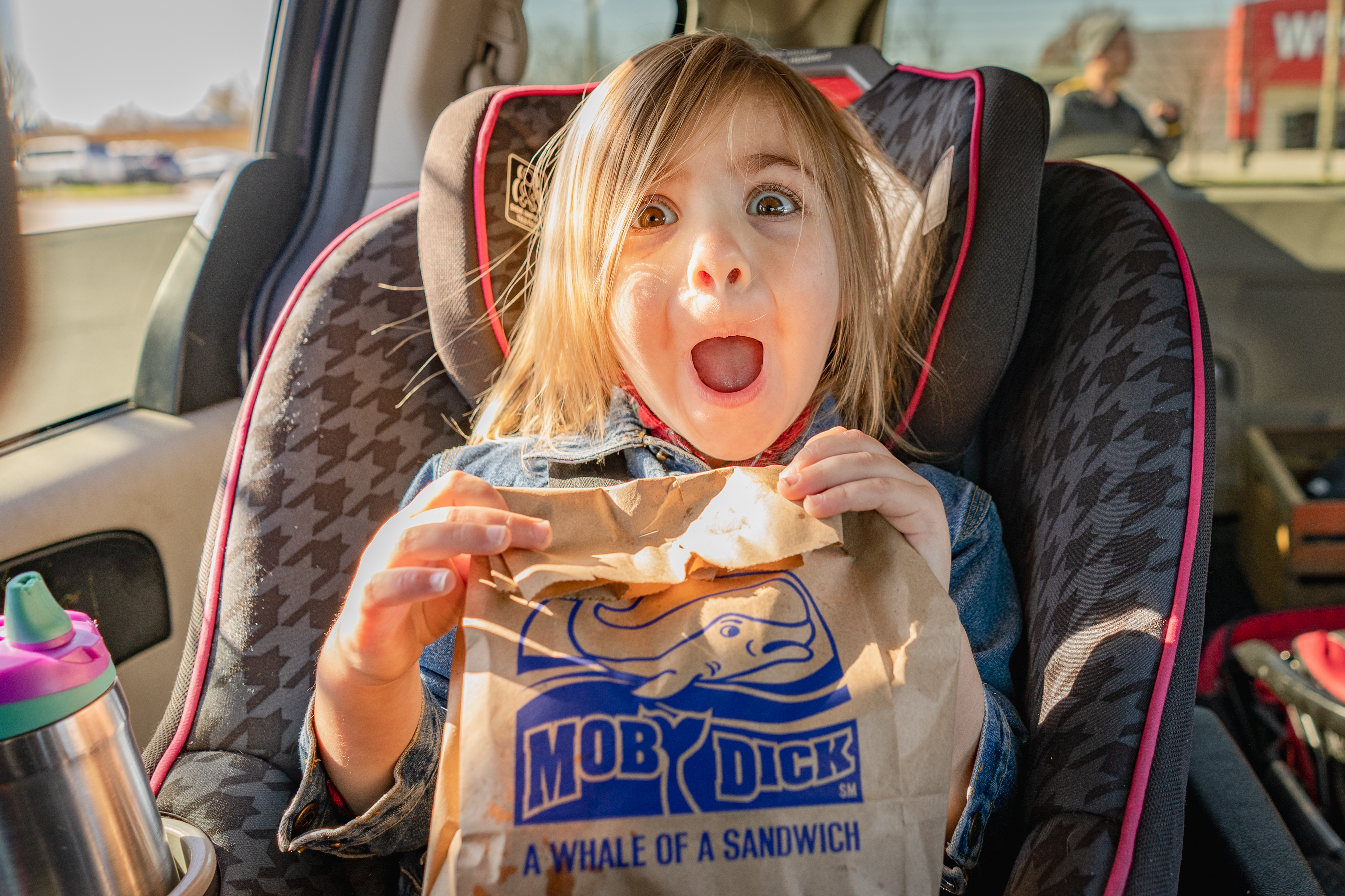 Little girl makes a happy face with a bag of fast food