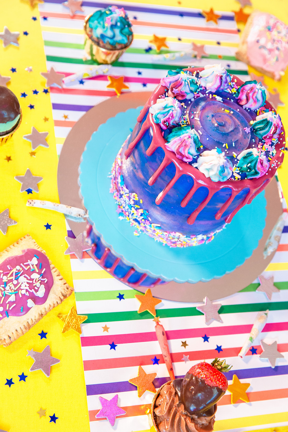 A colorful decorated cake on a table covered in decorations and other pastries