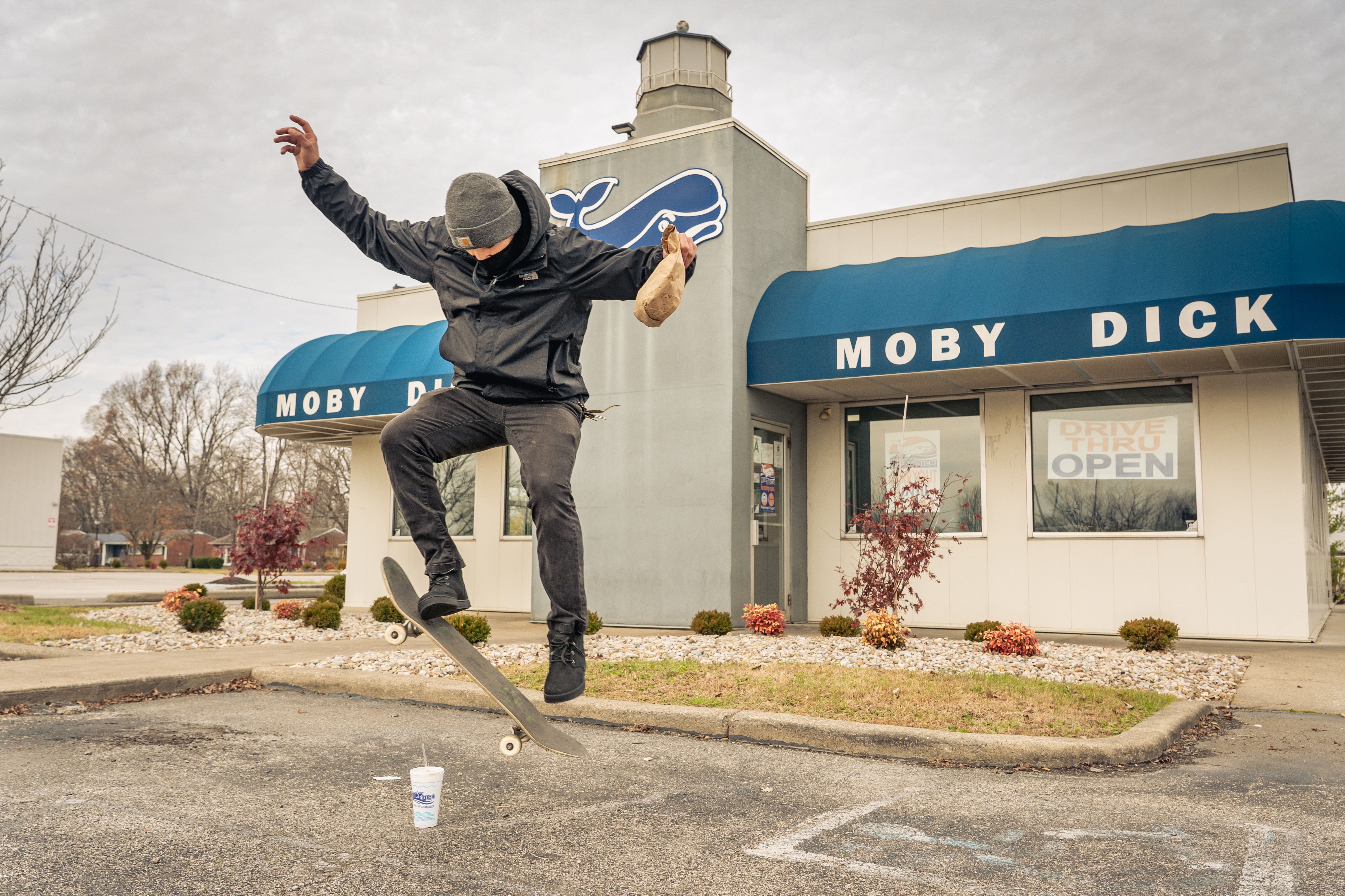 Skater jumps over a cup in parking lot