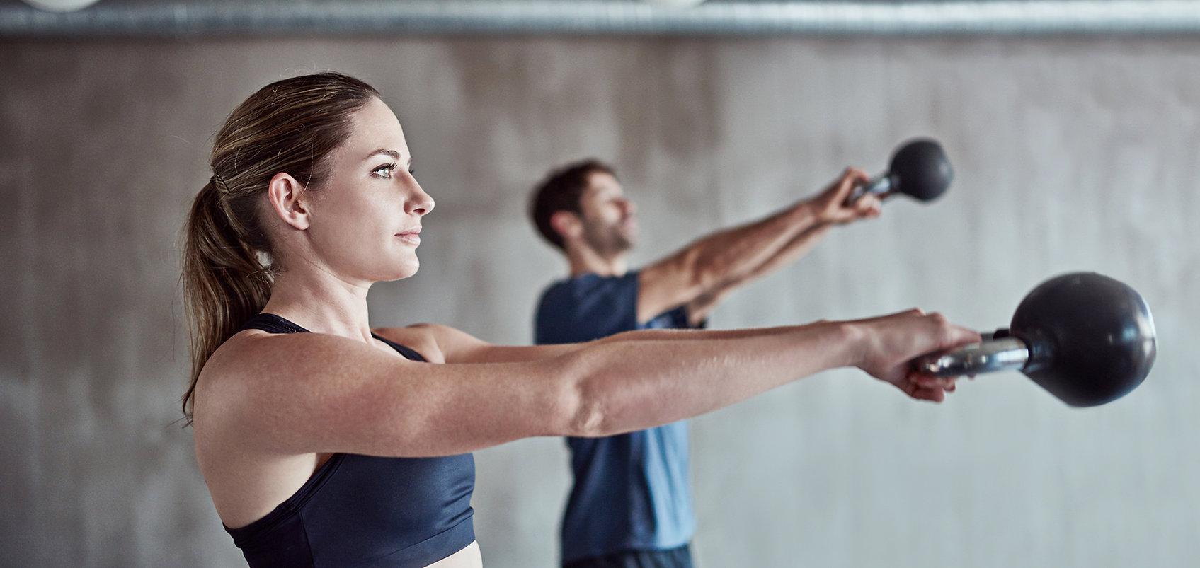 Fitness trainers swinging kettlebells.
