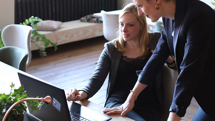 two-women-using-on-black-laptop-computer