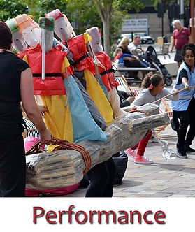 The audience help bring a driftwood boat carrying a cargo of puppets (representing migrants) into shore