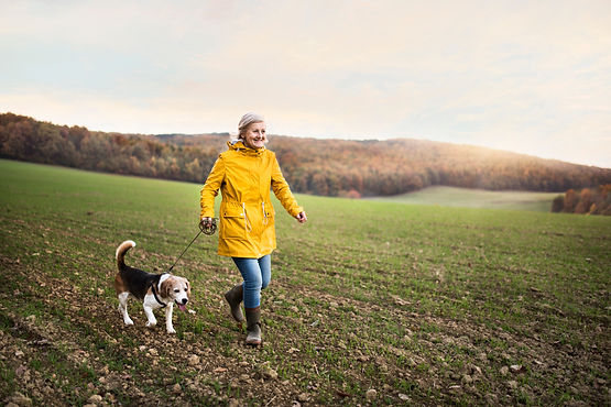 Senior woman with dog on a walk in an au