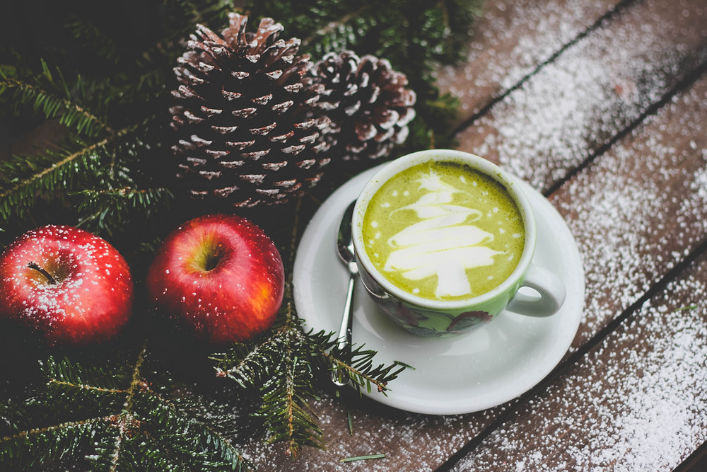 Christmas latte sitting on table with arrangement of apples, pinecones, and evergreen sprigs