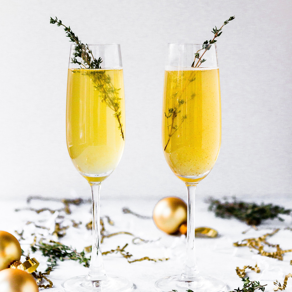 2 beverages in a champagne flute with rosemary