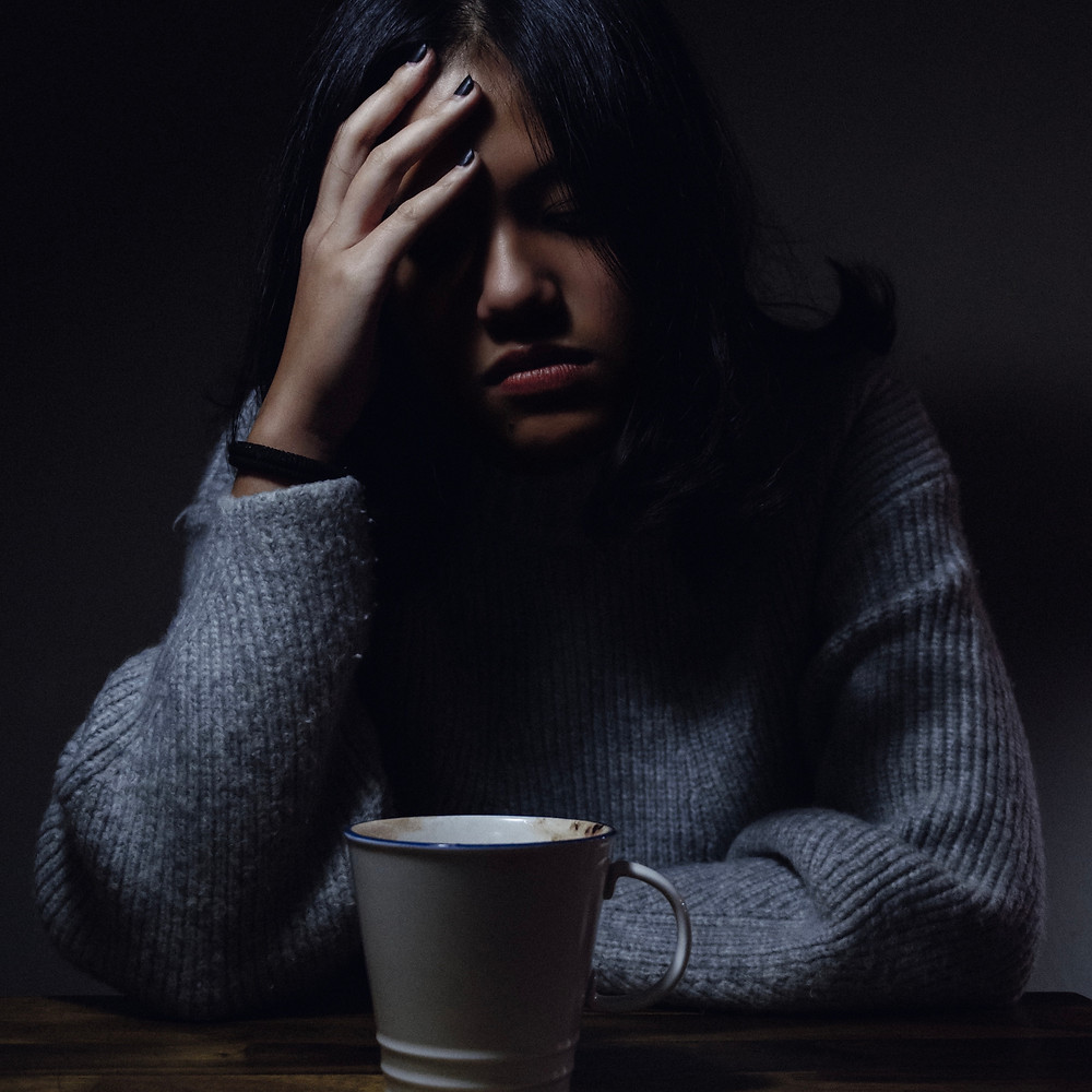 stressed woman with hand on her forehead and cup of coffee in front of her