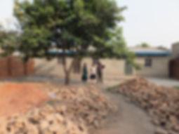 benjamin showing us building grounds.JPG