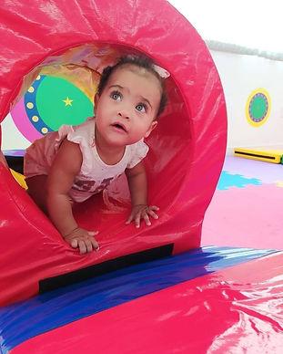 Criança passando por dentro de um túnel de borracha