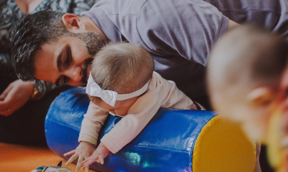 Pai brincando com a filha em aula de estimulação