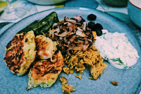 Courgette and manouri fritters with mujadara and tzatziki