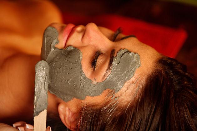 Mud facial mask of woman in spa salon. B