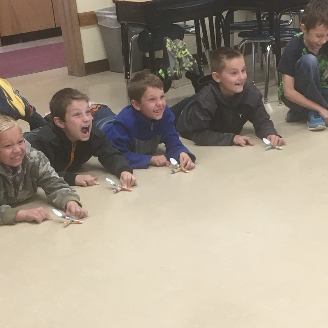 The students line up on the classroom floor to test their catapults for the force and motion lesson.