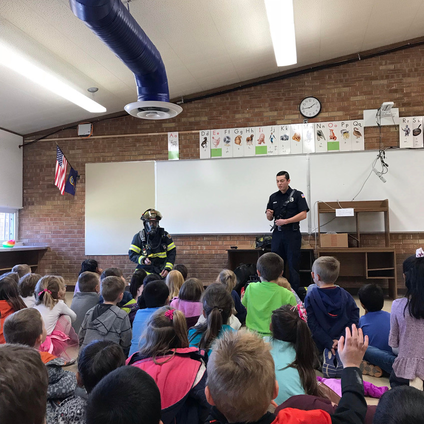 Firefighters teach 2nd Grade students fire safety.