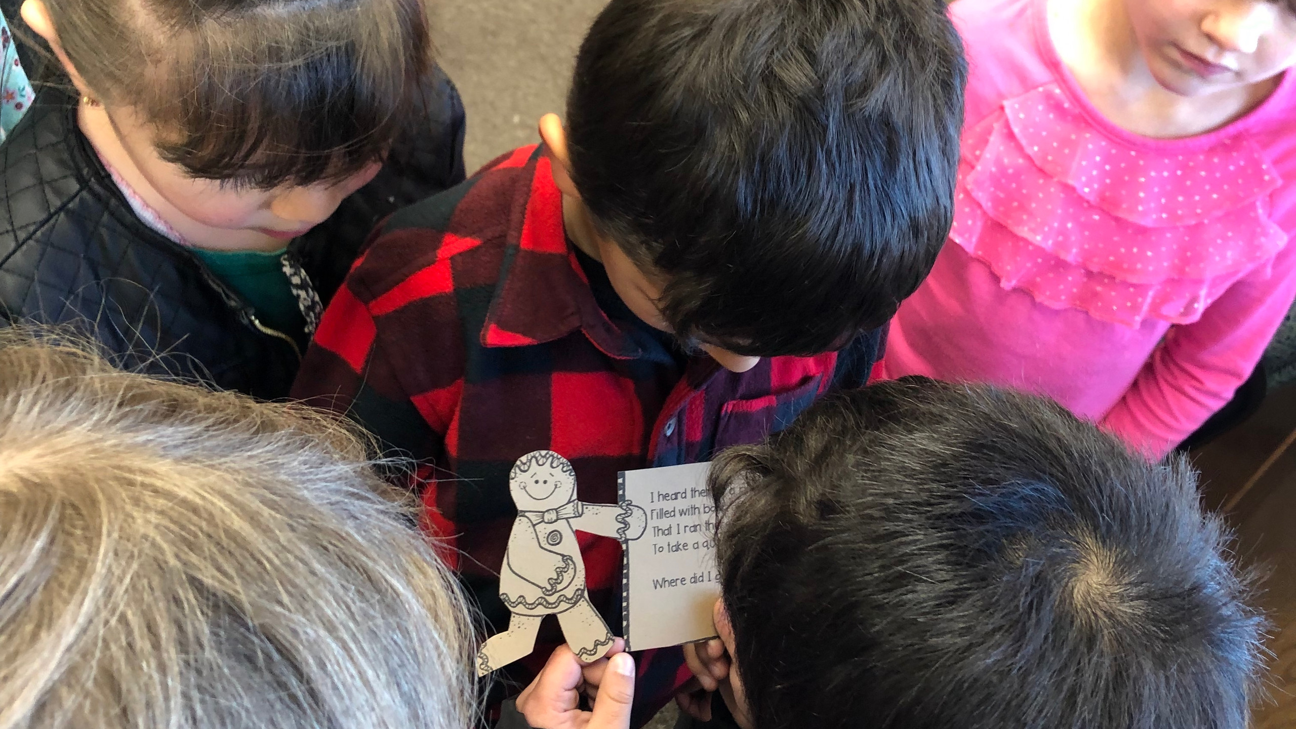 Kindergarten Class Students huddle to find out the next clue to the Gingerbread Man.