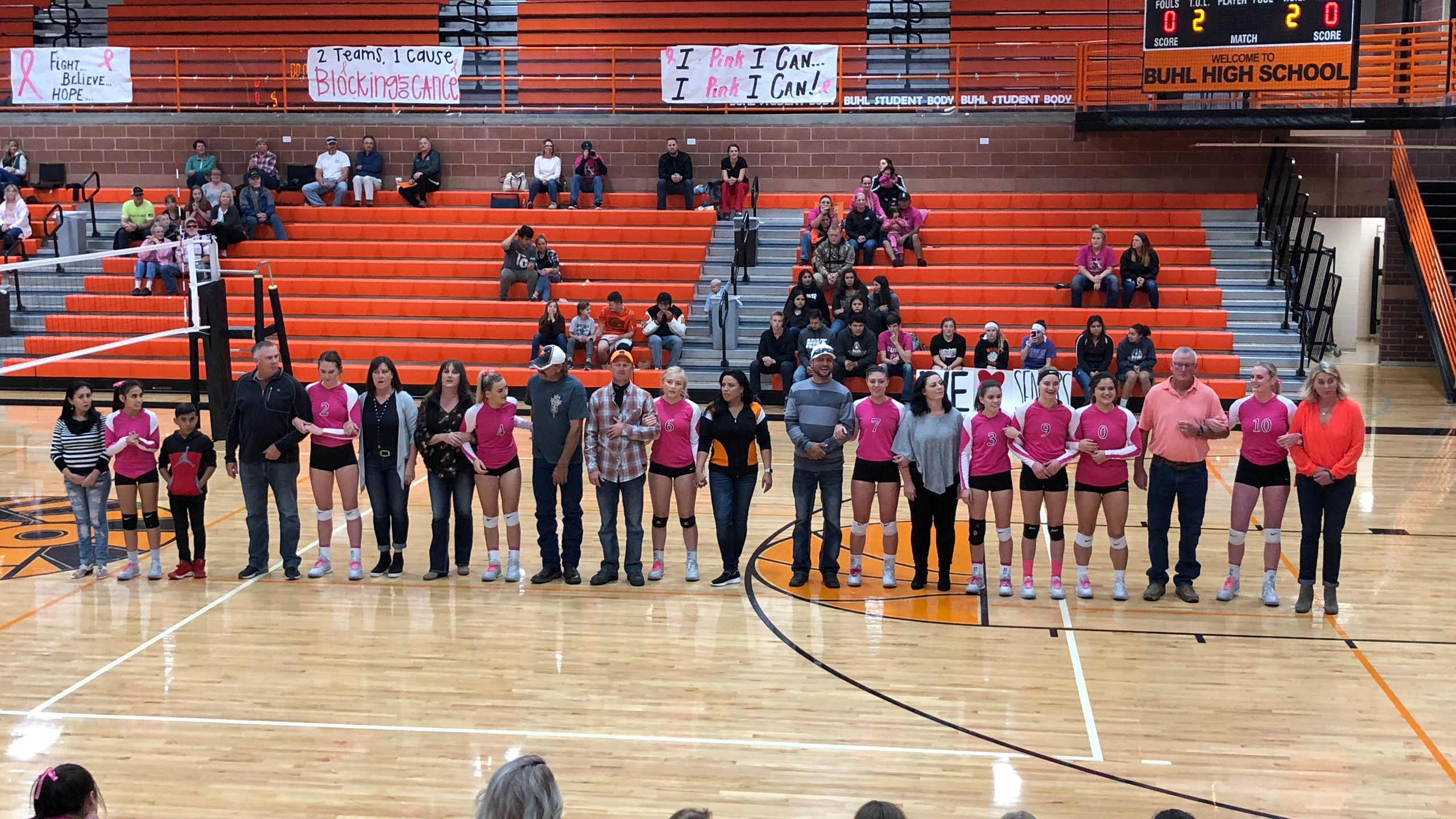 Senior Girls stand with their parents as they get recognized for their last home game. They are wearing their pink jerseys to support cancer awareness.