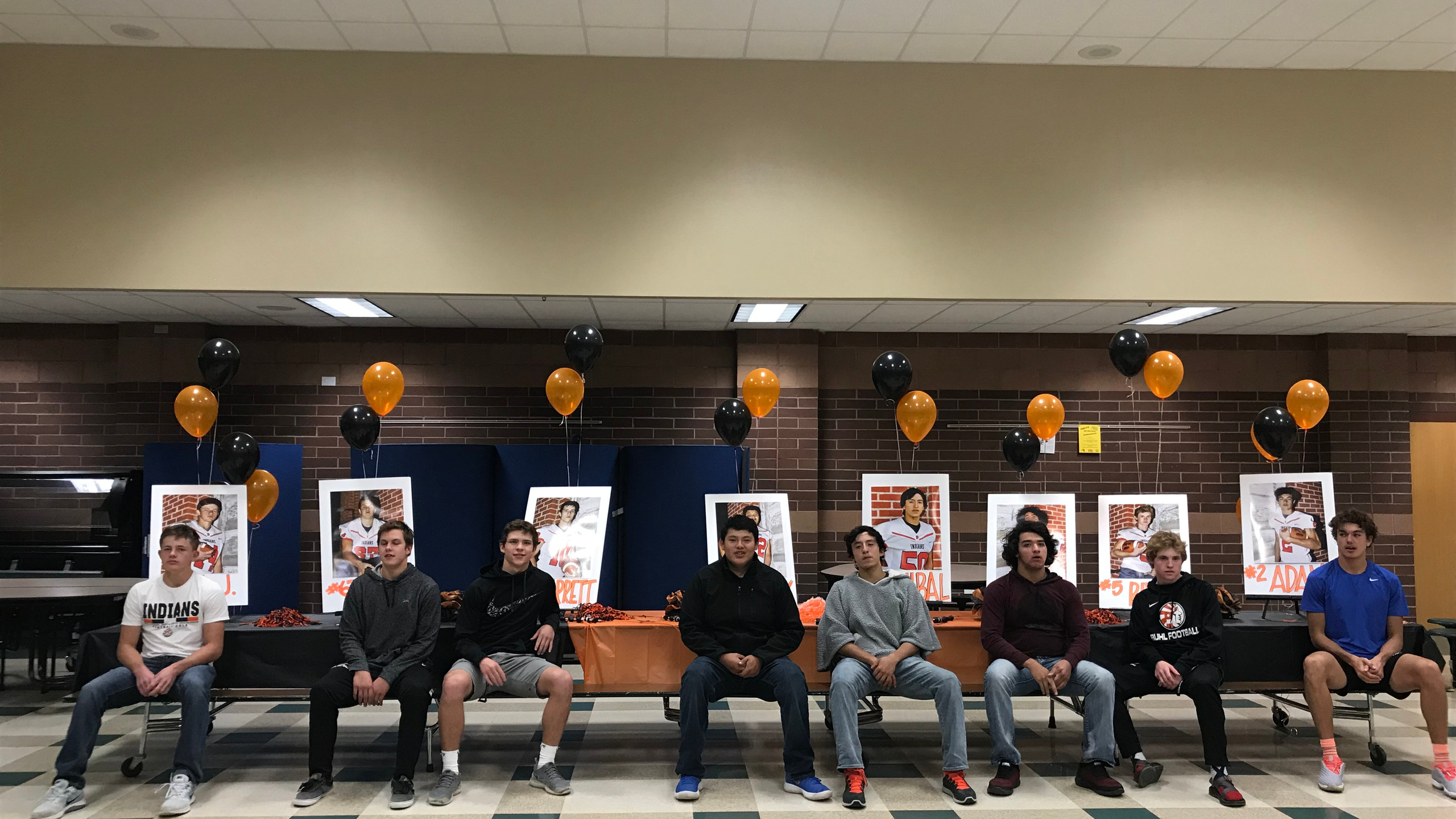 The 8 Senior Boys take a picture together in front of their portraits and balloons.