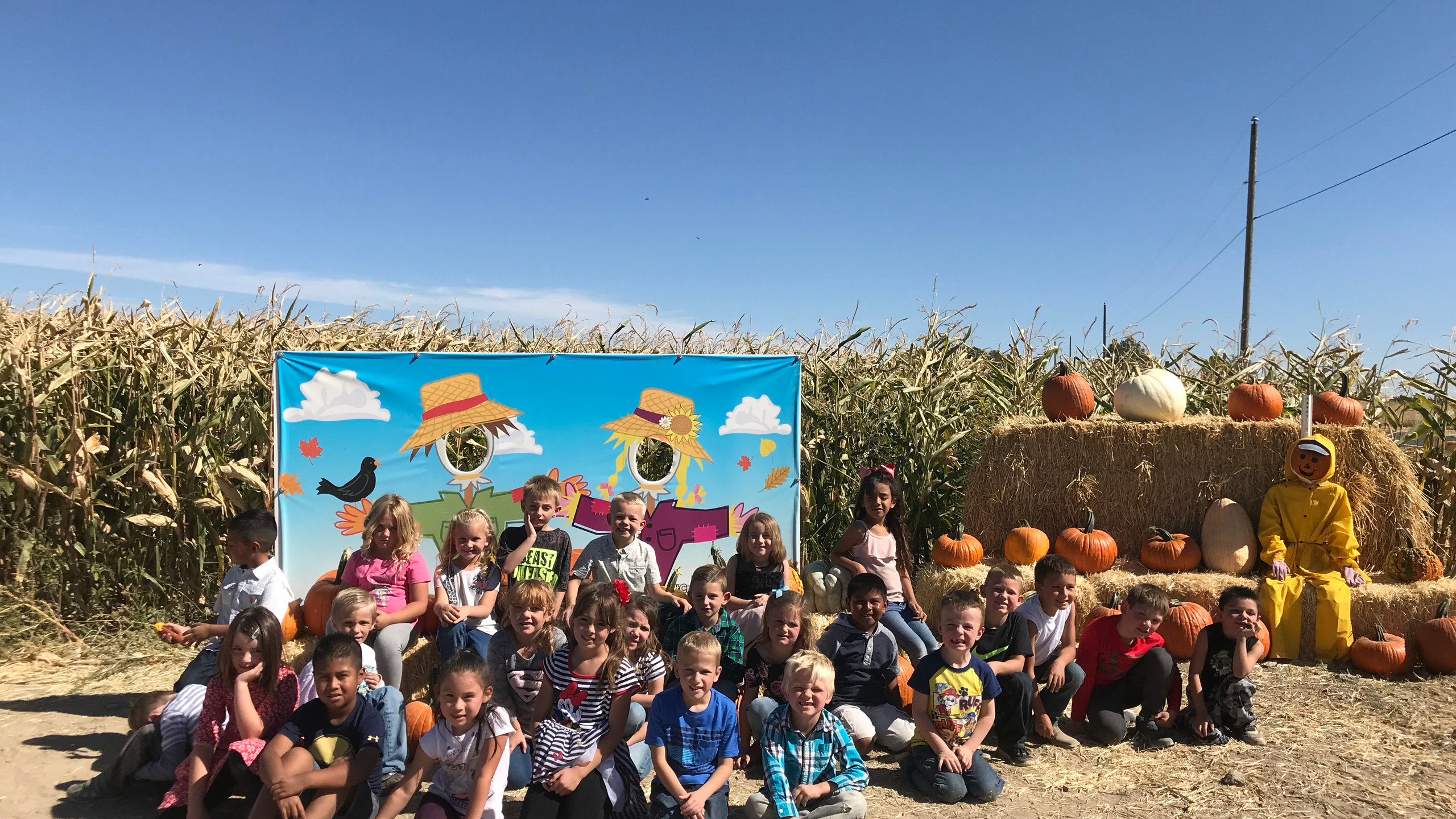 PES Students pose in front of scarecrow picture booth.